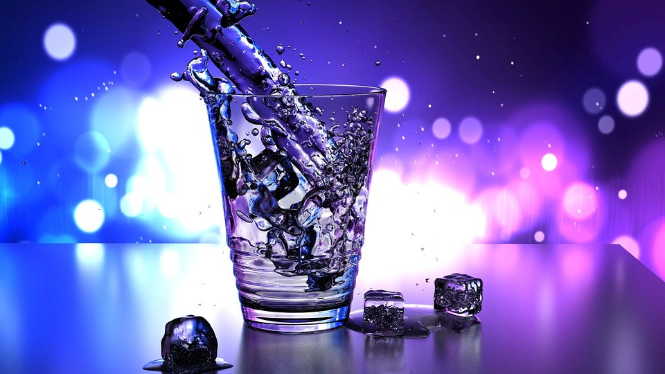splashing water into a clear cup with ice and blue and pink light background