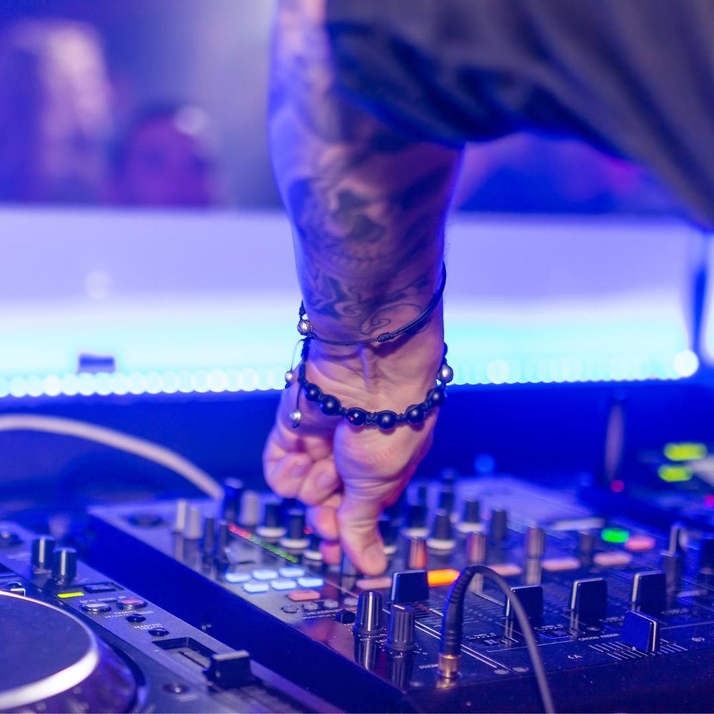 dj mixing music in blue lighting with hand on knobs
