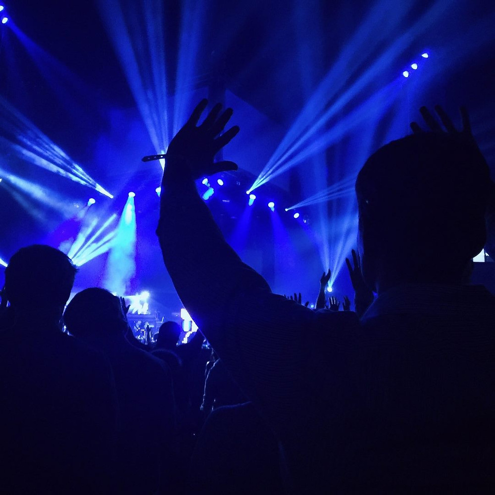 hands waving in air with blue stage lights in front