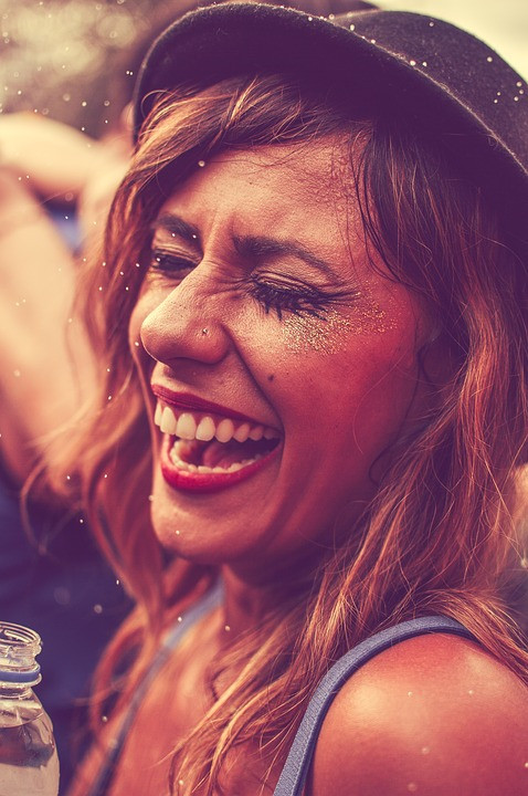 girl laughing at festival with glitter on her cheeks and hair