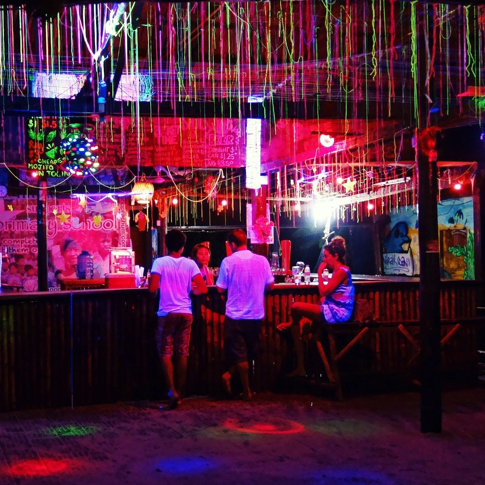 neon colorful bar with 3 figures at the bar