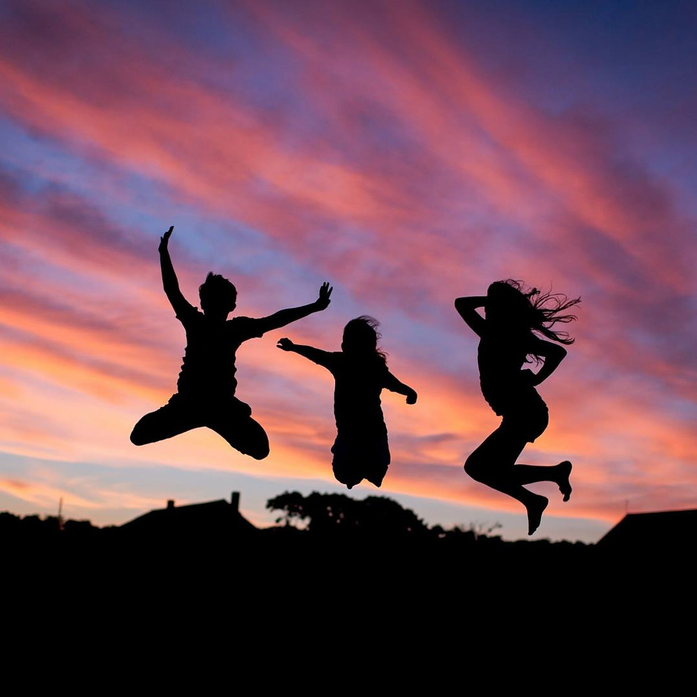brilliant pink sunset behind 3 silhouette figures of children dancing and jumping