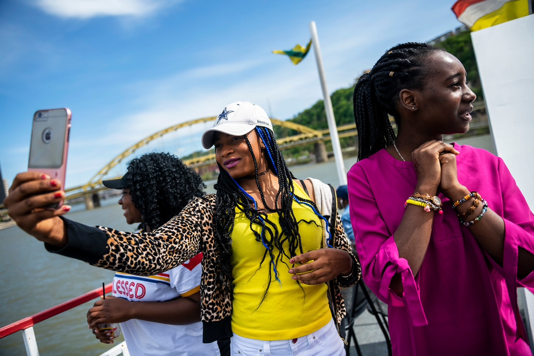 Deborah Mwadi, of the North Side and originally from the Congo, left, looks at the city skyline while Elizabeth Masanka, of Northview Heights and originally from the Congo, center, takes a selfie and Blessing Yava, of the Hill District and originally from Namibia, right, talks to friends while taking a boat cruise, Saturday, April 27, 2019, on the Clipper Gateway on the Allegheny River. Riverlife and Hello Neighbor teamed up for the past three years to welcome immigrants and refugees to Pittsburgh with a two hour cruise introduce them to the city.