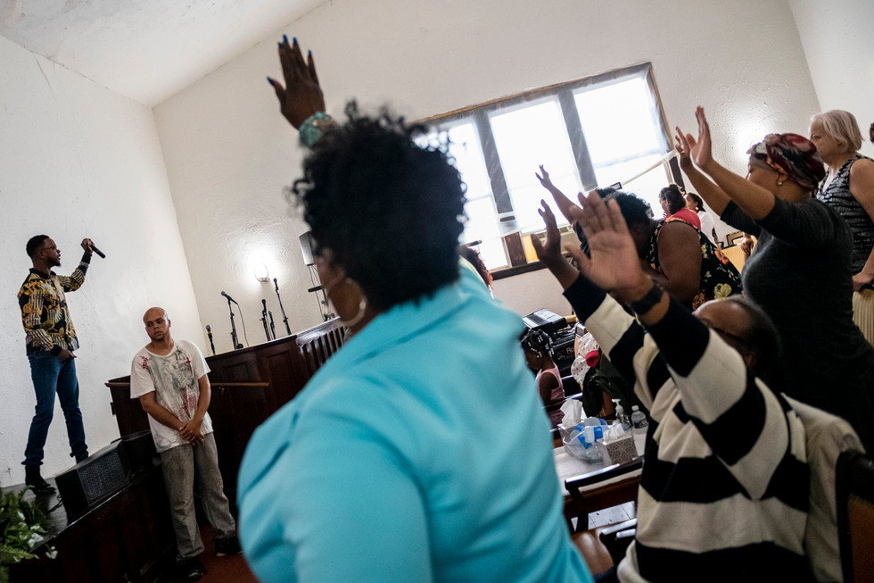 """Pastor Michael Day, of Beltzhoover, left, preaches as parishioners raise their hands in prayer during the """"Hour of Power"""" service, Thursday, June 20, 2019, at Legacy International Worship Center in North Side. On Wednesday June 19, Syrian refugee Mustafa Mousab Alowemer was arrested by the FBI Wednesday June 19 and accused of planning to put a bomb in the church next month in support of the Islamic State of Iraq."""