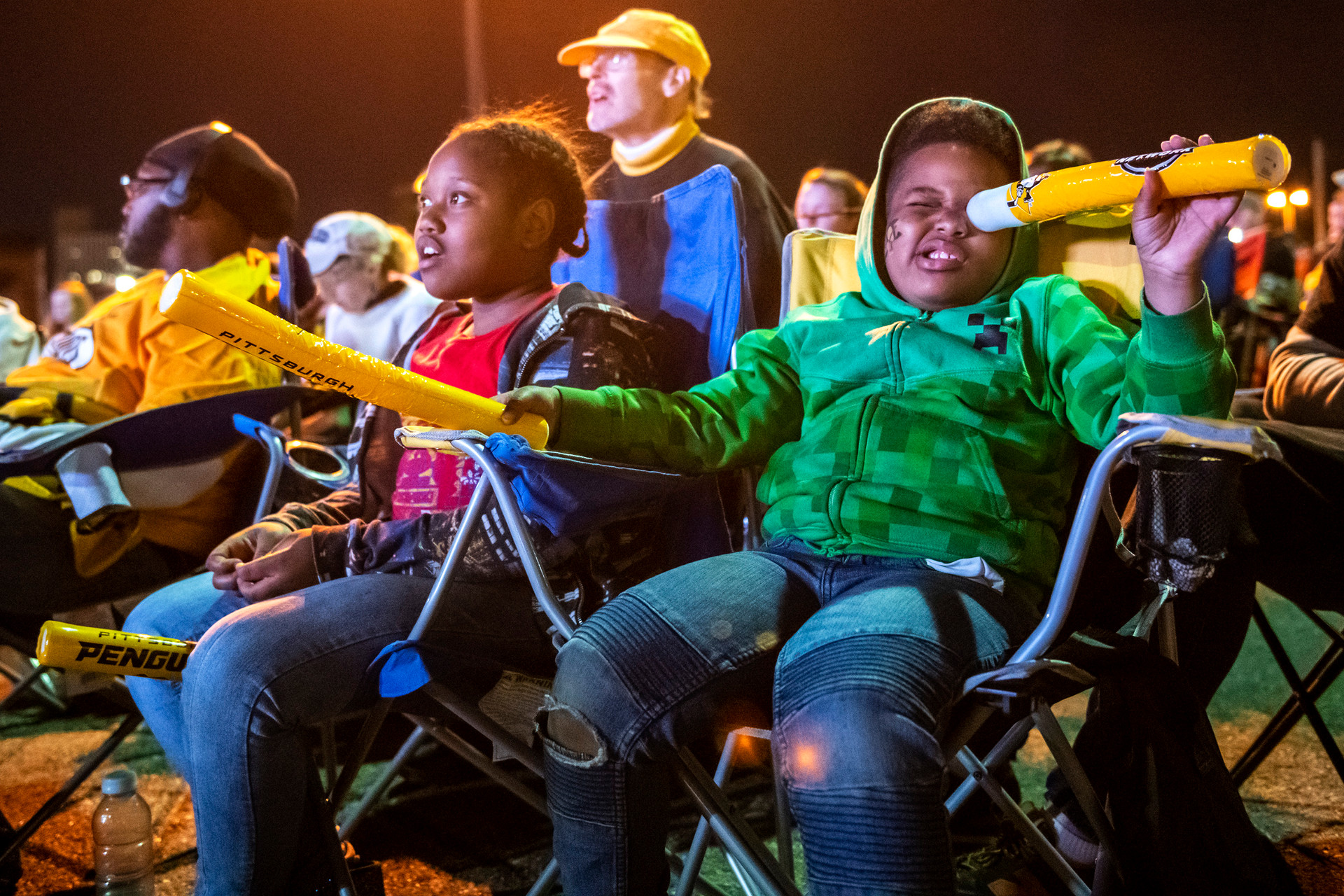 Tyler Norman of the Hill district, left, watches the first-round playoff series between the Pittsburgh Penguins and New York Islanders on the big screen as his brother Tyrone Norman of the Hill, right, looks through a Penguins souvenir given to fans, Tuesday, April 16, 2019, at the PPG Paints Arena parking lot in Uptown.