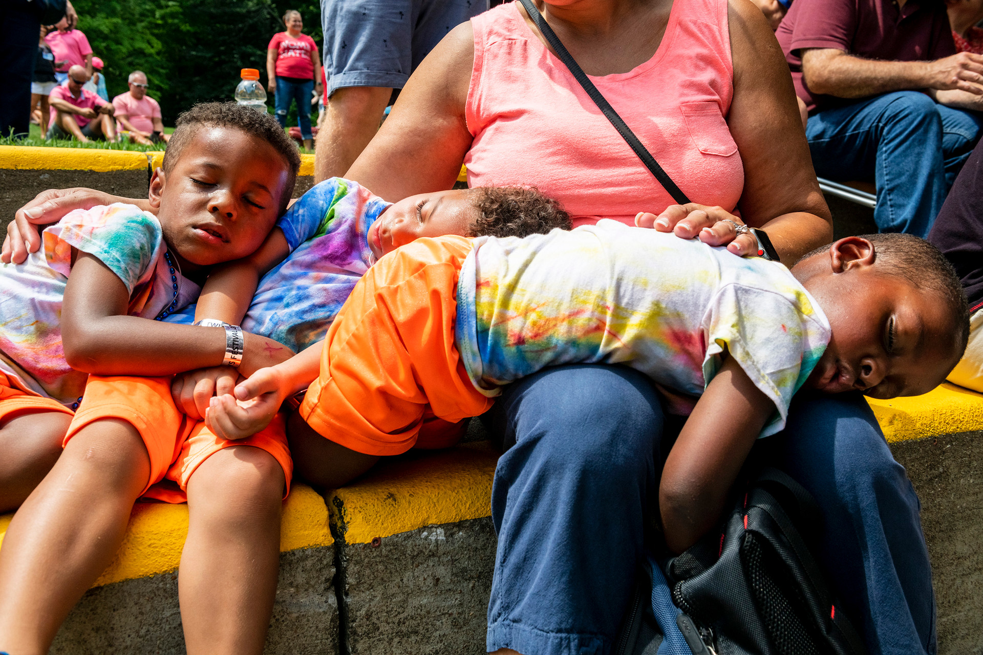 """Daniel Clark, 3, left, his twin brother Gabriel Clark, 3, center, and Samuel Clark, 2, right, all of the North Side, sleep on their grandmother Robin Hubbard, of Sewickley,   while waiting to watch their twin siblings participate in the costume contest at the 44th annual Twins Days Festival, Saturday, August 3, 2019, in Twinsburg, Ohio. The annual international event is recorded as the """"Largest Annual Gathering of Twins in the World"""" by the Guinness Book of World Records."""