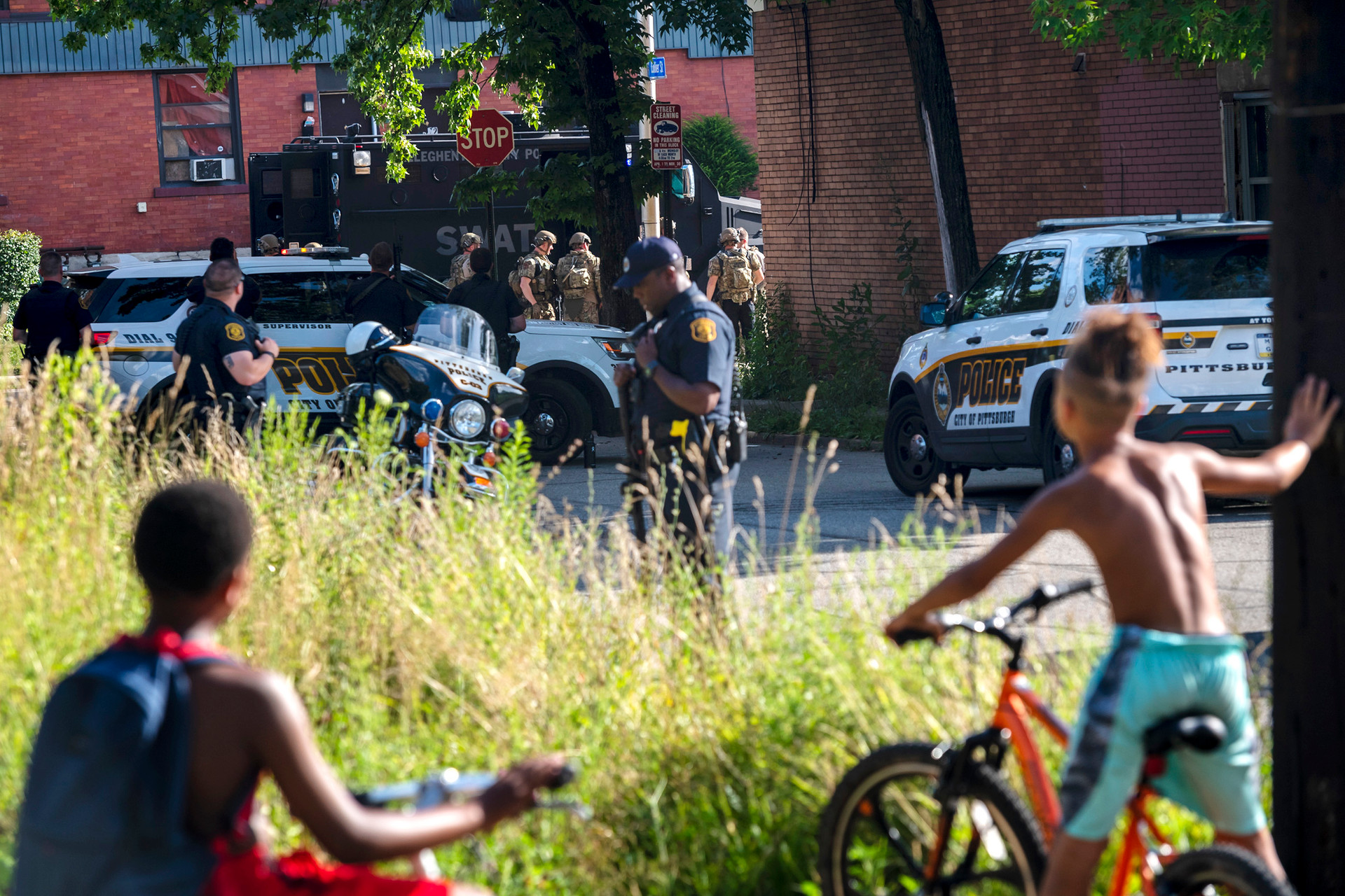 Children watch as a SWAT team arrives to lend support to City of Pittsburgh Police officers as they attempt to serve an arrest warrant, Tuesday, July 16, 2019, on the intersection of Collier Street and Hamilton Avenue in Homewood.