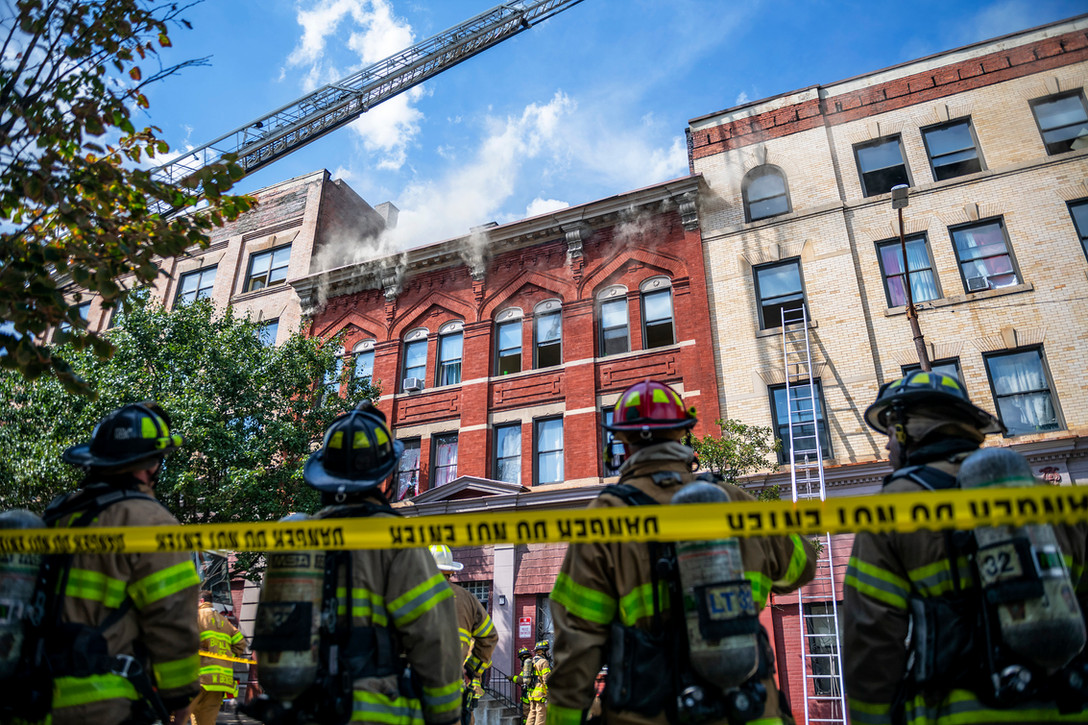Firefighters watch as smoke begins to pour out of building  during a five alarm residential fire, Saturday, August 17, 2019, on the 2000 block of Deraud Street in West Oakland.