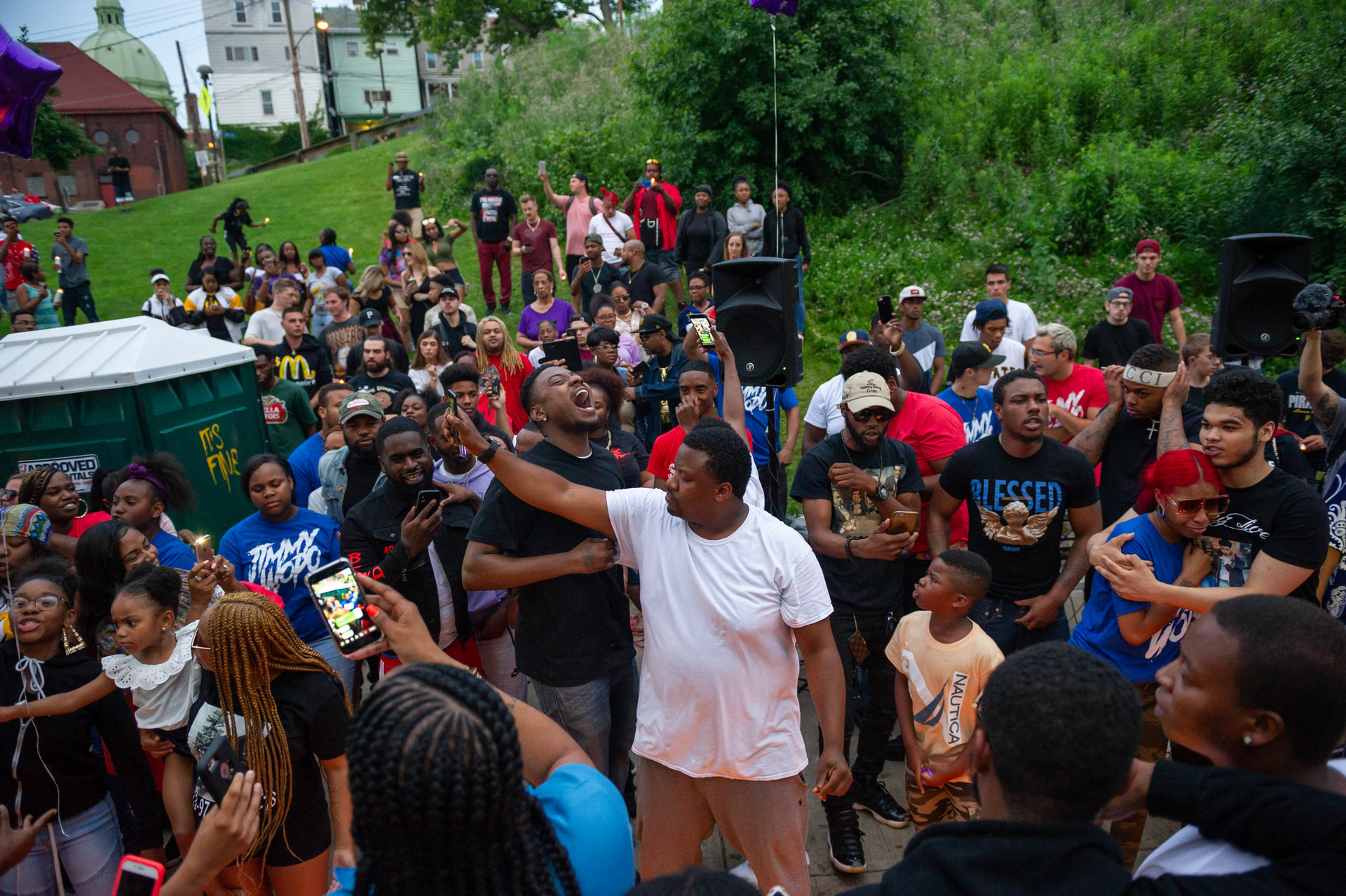 Pittsburgh rapper Jimmy Wopo's brother Juawane Dennison, from the Hill District, center, sings along to his brother Jimmy's music surrounded by friends and fans of the rapper during a vigil for the slain rapper at West Penn Park on Thursday June 21, 2018, in Polish Hill. Jimmy Wopo was fatally shot on Monday June 19 in the Hill District.