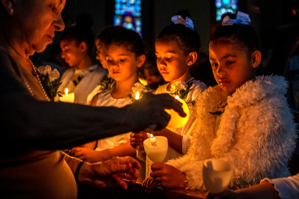 Andrea Urban, of Homestead, left, lights the candle of Halle Fincik, of Homestead, right, during a mass commemorating Easter, Saturday, April 27, 2019, at St Nicholas Orthodox CR Church in Homestead. Orthodox Christians around the world commemorate Easter Sunday April 28. The Orthodox use a different method for calculating the date of Easter than Western Christians which can often land on different dates.