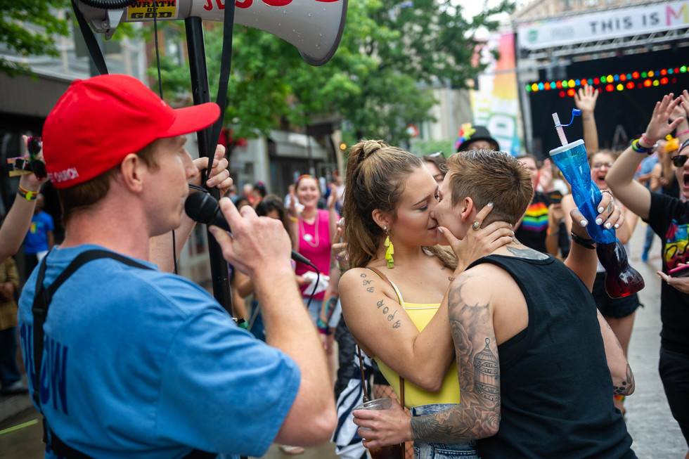 A pride protestor, who would not provide his name, speaks of Jesus and the Bible while Brittany Bloom, from Johnstown PA, and Billie Jo Thomas, from Johnstown PA, kiss during 2018 PrideFest on Saturday June 9, 2018, in Downtown Pittsburgh. PrideFest is a 2 day event that celebrates LGBTQA identity.