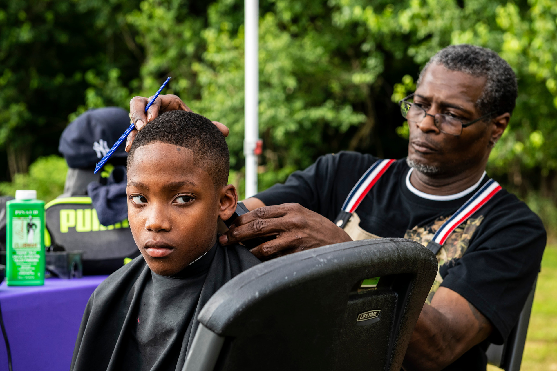 """Kross Boxley, 10, McKees Rocks, left, gets a haircut from Victor """"Roc"""" Miles Sr., of Braddock and barber at Unlimited Styles in Rankin, left, during the second annual Antwon Rose II Community Birthday celebration, Friday July 11, 2019, at Hawkins Village in Rankin. The Antwon Rose II Community birthday celebration featured food, vendors, bounce houses, live performances and a free book-bag giveaway for 250 youth."""