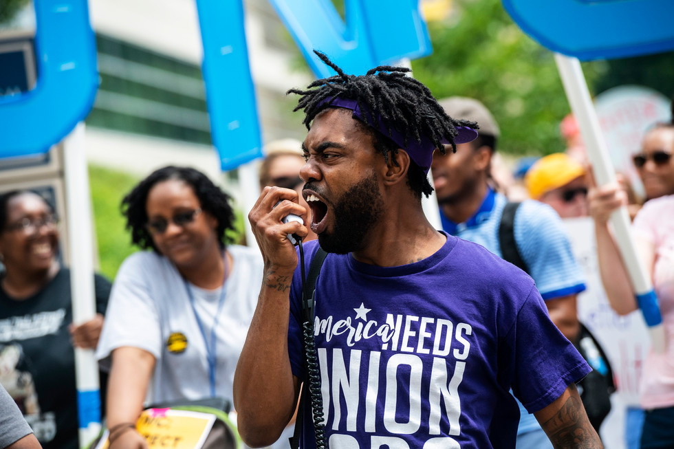 Damien Grayson, of the Hill District and a union organizer, leads protestors in a chant while marching during a UPMC workers strike, Tuesday, May 28, 2019, on Terrace Street in Oakland. Striking UPMC hospital workers, patients, and community leaders gathered to protest before a UMPC board public meeting to demand that UPMC protect patient access, end workers' rights violations, raise wages, and cancel worker medical debt.