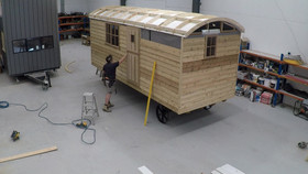 Shepherds hut being clad with cedar timber weatherboards in our factory