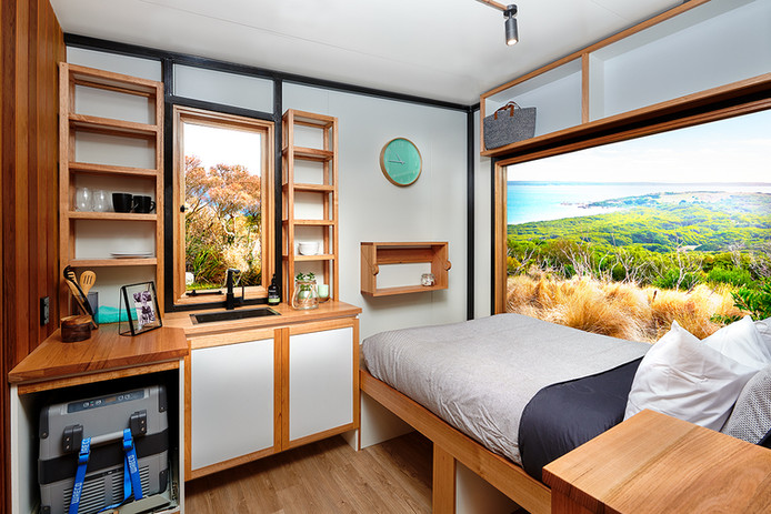 bedding in tiny house with pullout fridge