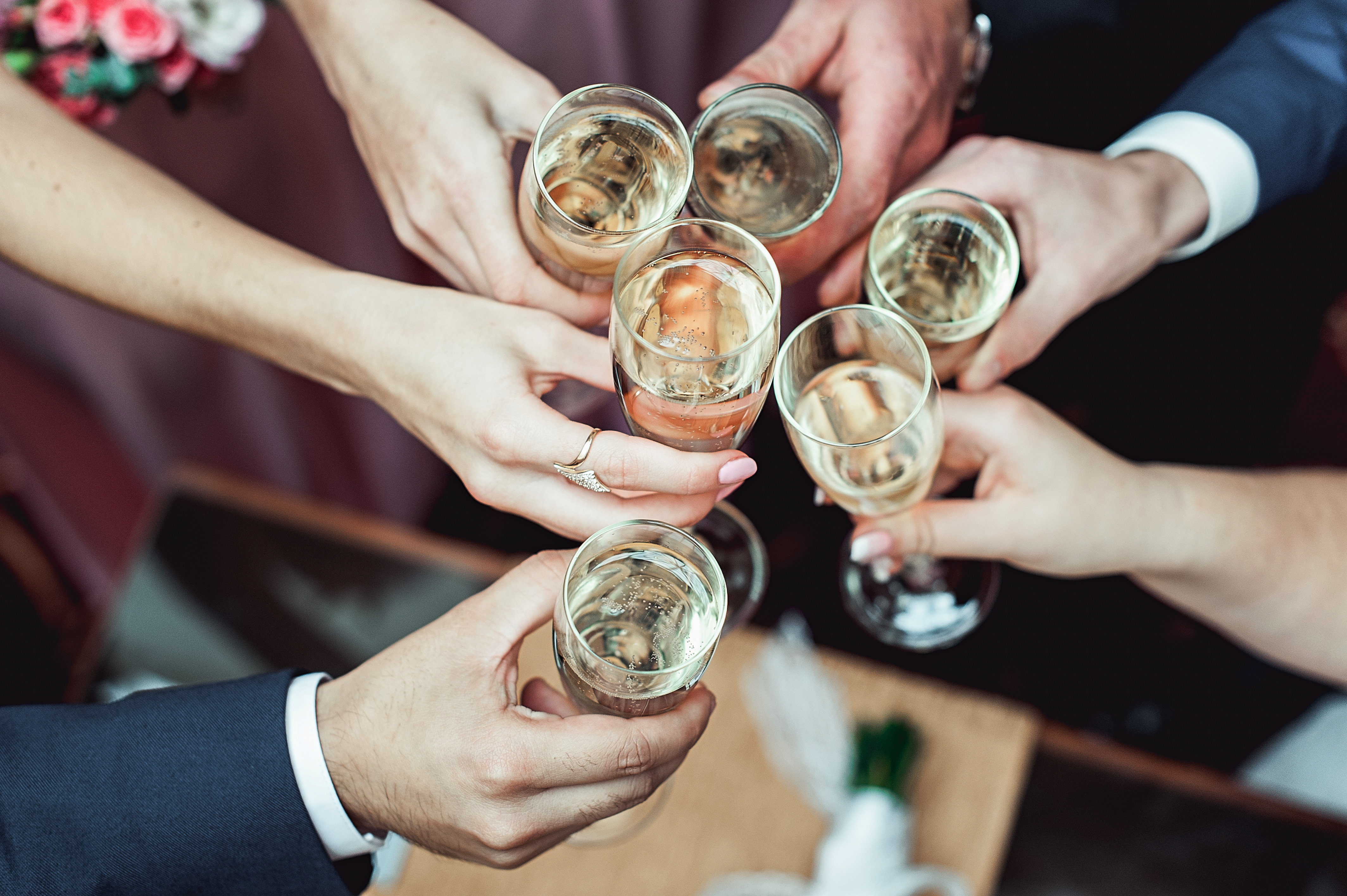 People-hold-in-hands-glasses-with-white-wine.-wedding-party.-659000066_4256x2832
