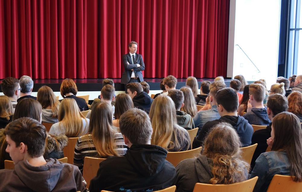 Jens Beeck sitzend vor Schülerinnen und Schülern.