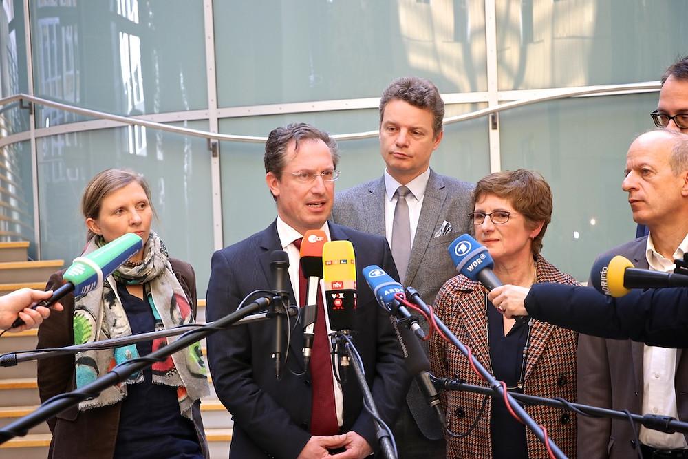 Jens Beeck und andere Abgeordnete vor Mikrofonen.