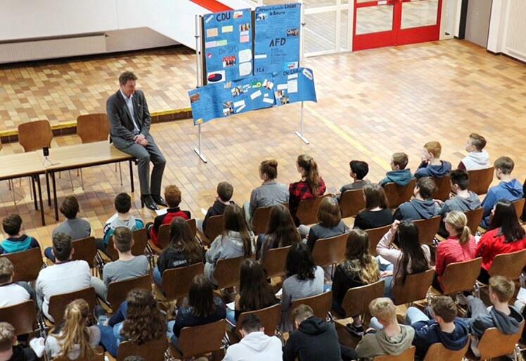 Jens Beeck sitzt vor Schülerinnen und Schülern.