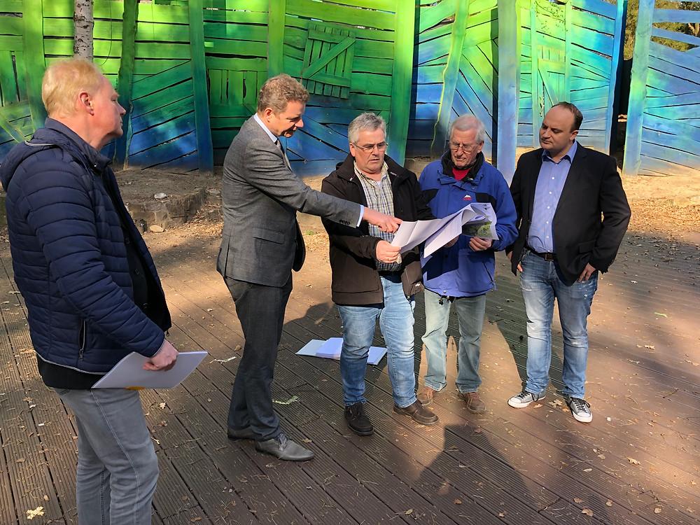 Jens Beeck betrachtet gemeinsam mit anderen Baupläne.