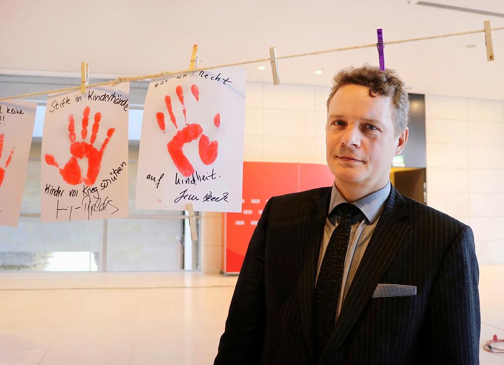 Jens Beeck neben einem roten Handabdruck auf einem weißen Blatt.