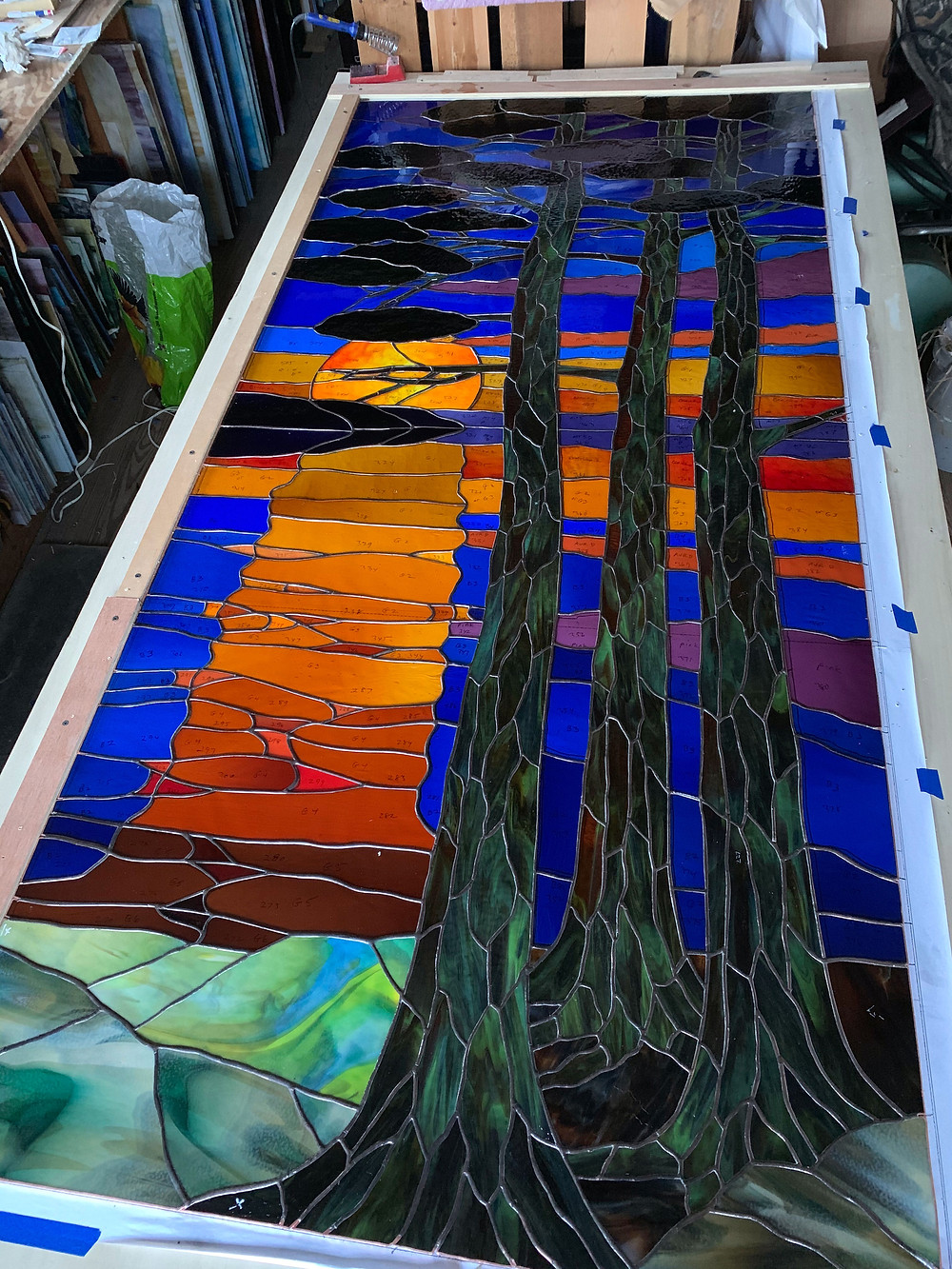 long stained glass window of pine trees by Anne Ryan Miller