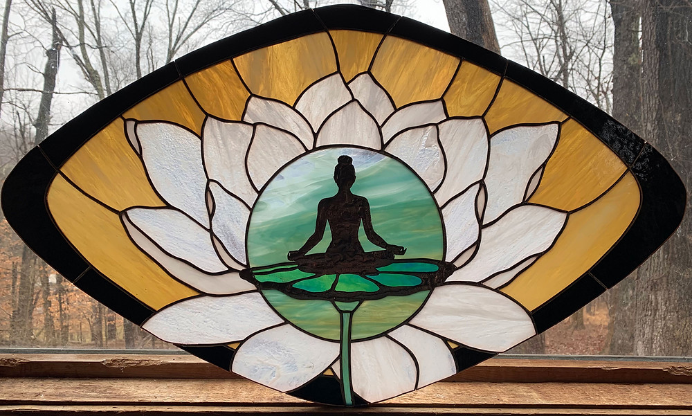 stained glass piece of seated yoga figure over a lotus blossom | © Anne Ryan Miller