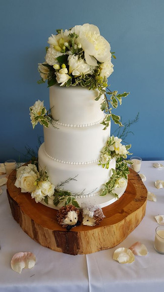 Iced Three tier with fresh flowers Wedding Cake