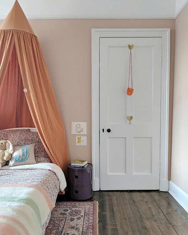 Girls bedroom with pink walls, orange bed canopy and purple componibili