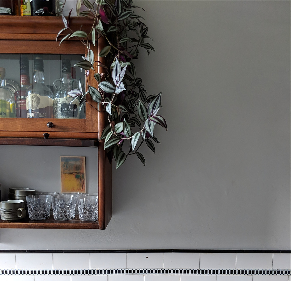 In a greyish blue kitchen, a tradescantia plant grows down from the top of a wall mounted, vintage glass cabinet. There are crystal glasses and bottles of drink in the cabinet.