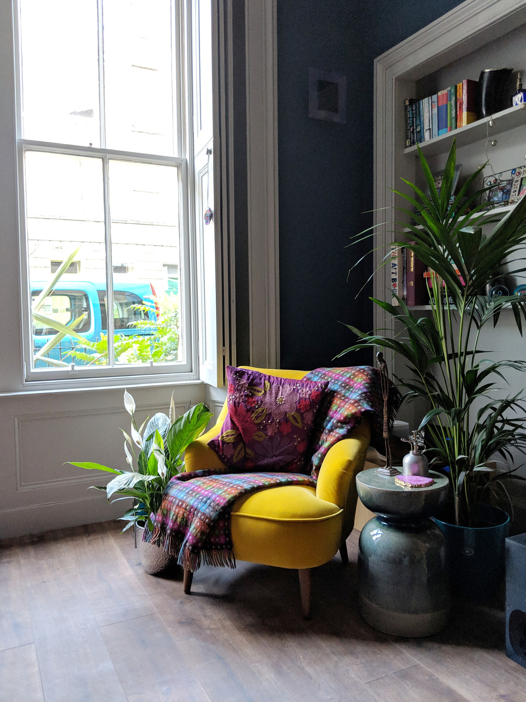 Yellow armchair styled with plants and bright accessories