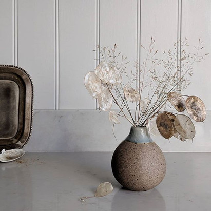 Sprigs of Honesty seed pods and grasses in a ceramic bud vase.