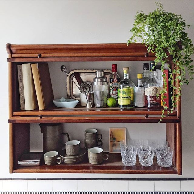 Vintage cabinet on kitchen wall styled with bar accessories and plant