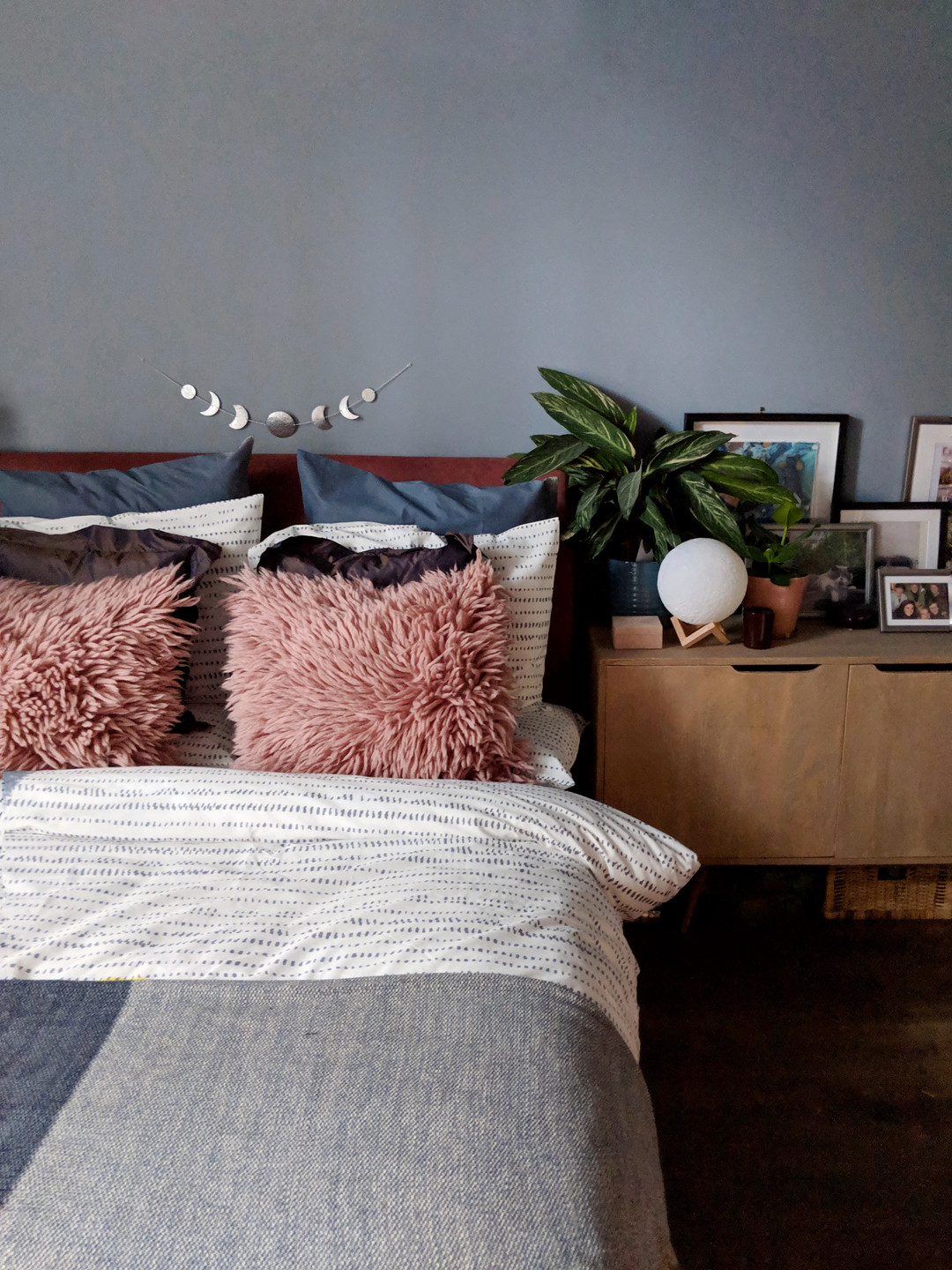 Comfy pillows styled on bed with sideboard dressed with many photos and plants