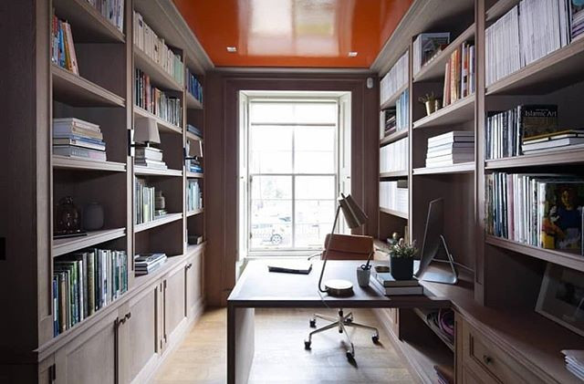 Wooden shelved study with built in desk. Shelves are full of books and objects. The ceiling is orange,