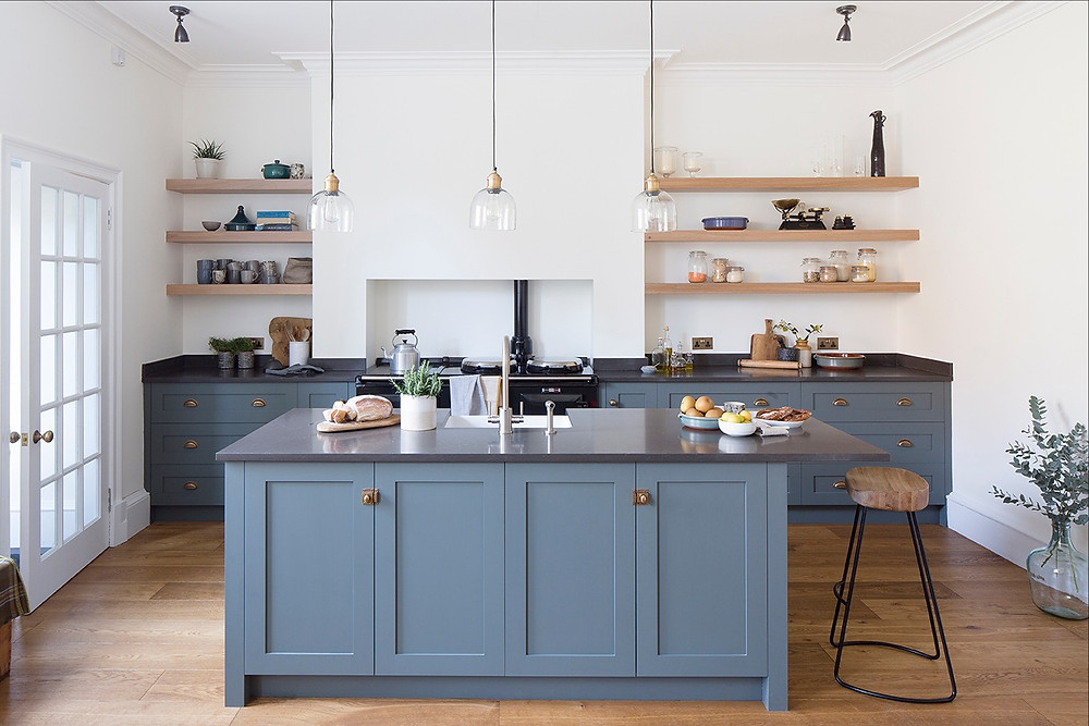 Dark blue Shaker style bespoke kitchen styled for photograph.