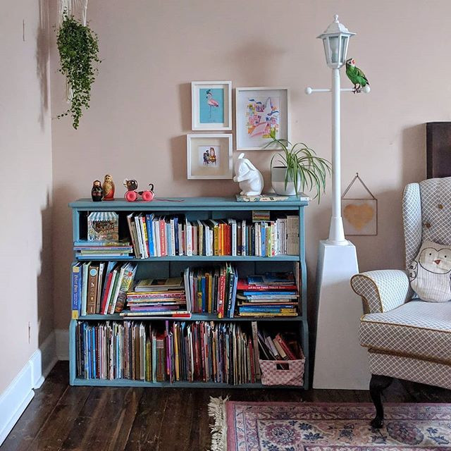 A children's bookcase painted blue in a girls' pink bedroom. There is a reading chair, a lamp that looks like an olden days street lamp and hanging plants.