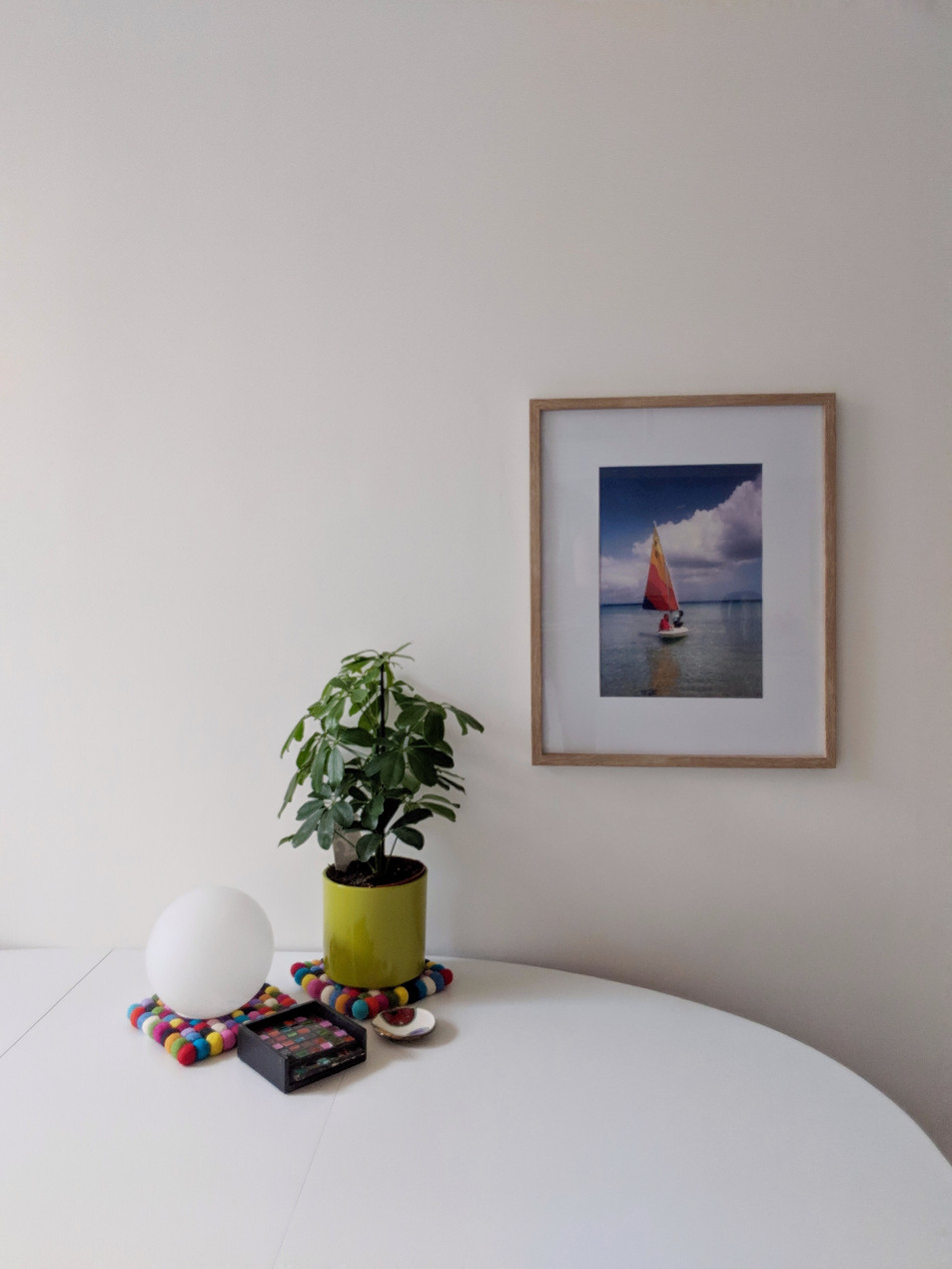 White table in a white room with a plant and a framed print on the wall