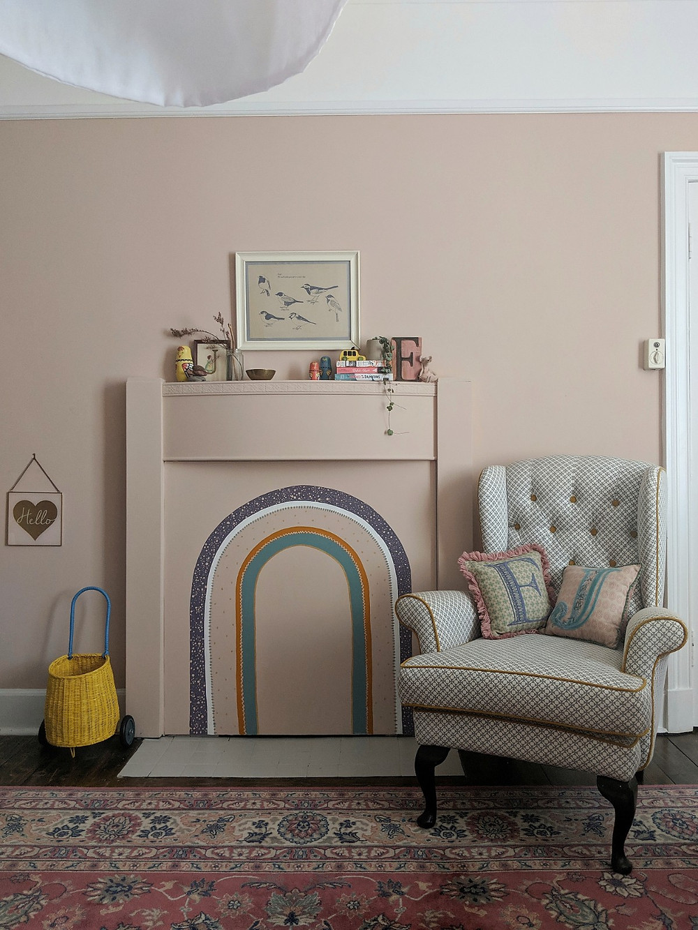 Girls bedroom fireplace painted pink with a rainbow