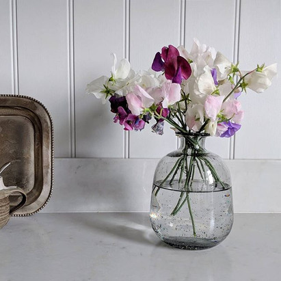 Garden-picked sweet peas in a clear vase on a kitchen counter.