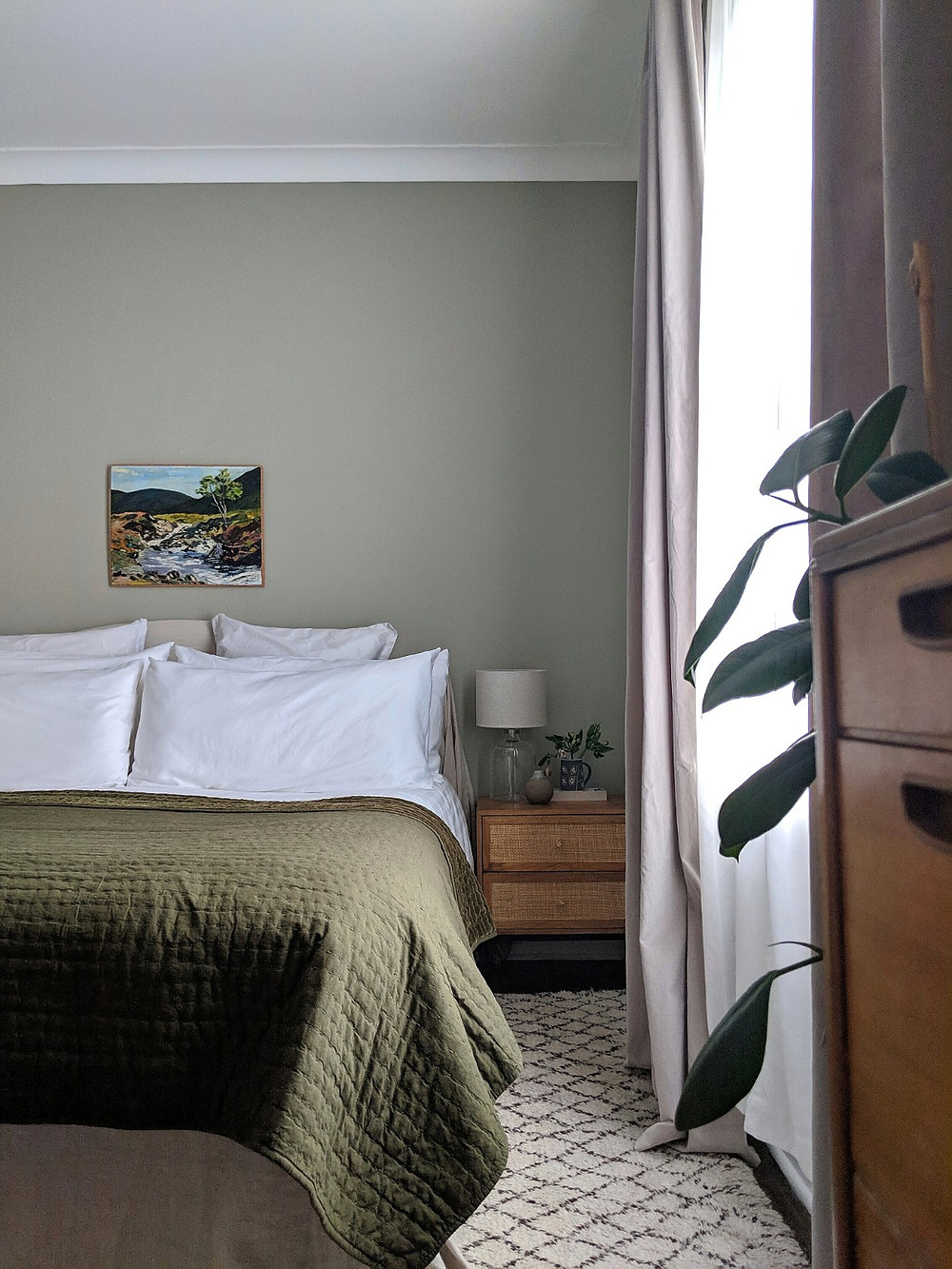 bedroom; dark green bedspread, soft green walls, bedside table (maison du monde Helios), glass bedside lamp, plants.