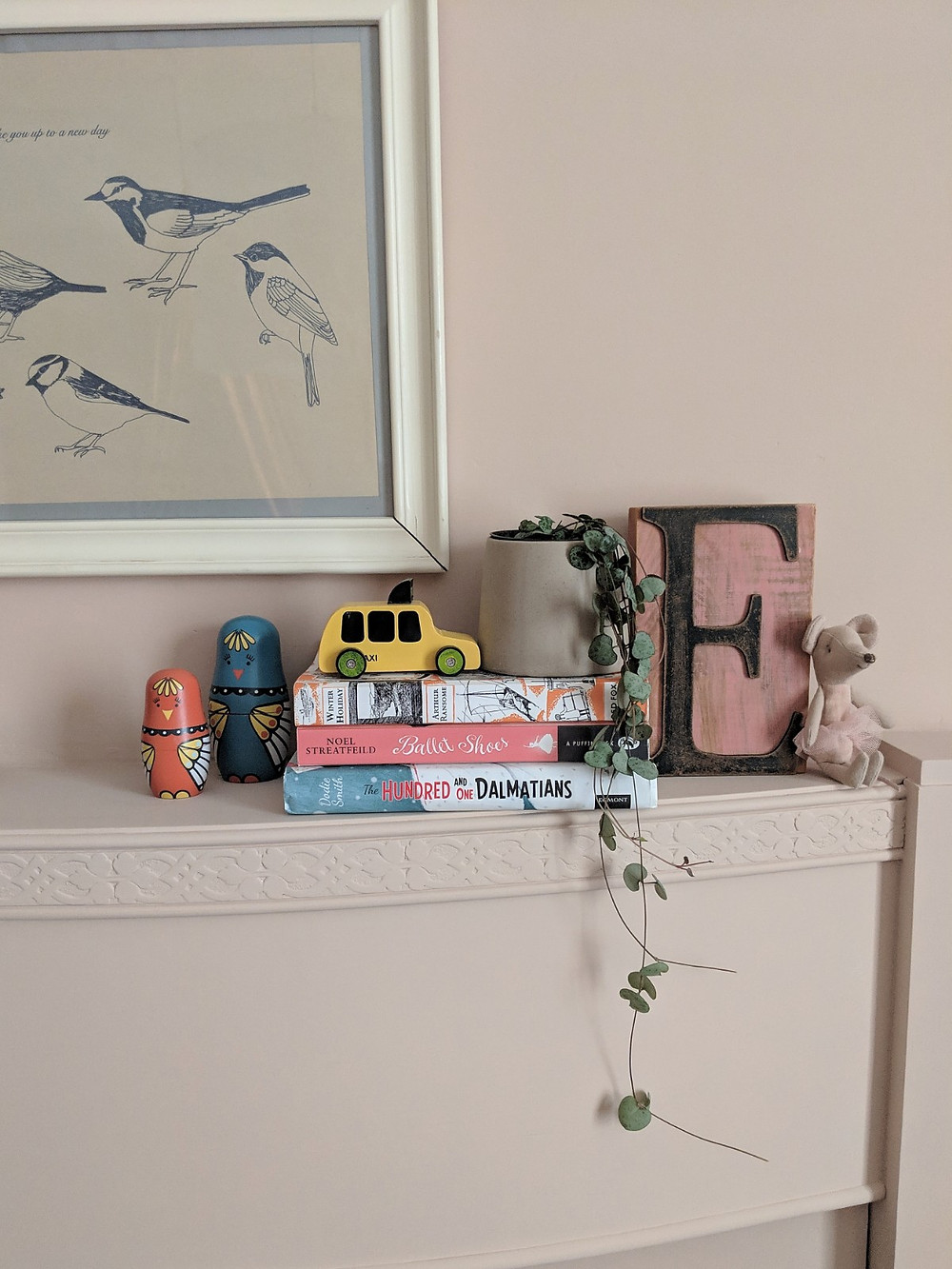 Children's objects arranged on a pink mantlepiece