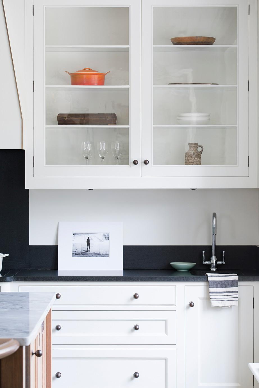 White glazed upper kitchen cabinets, dark worktop.