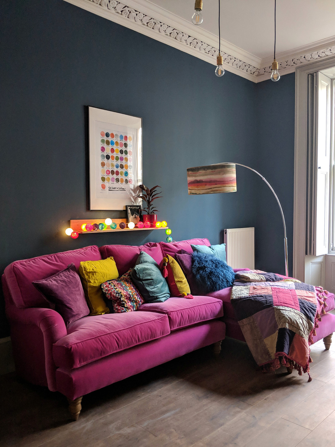 Bright pink sofa.com bluebell chaise with a dark blue wall and 50 shades of Scotland print