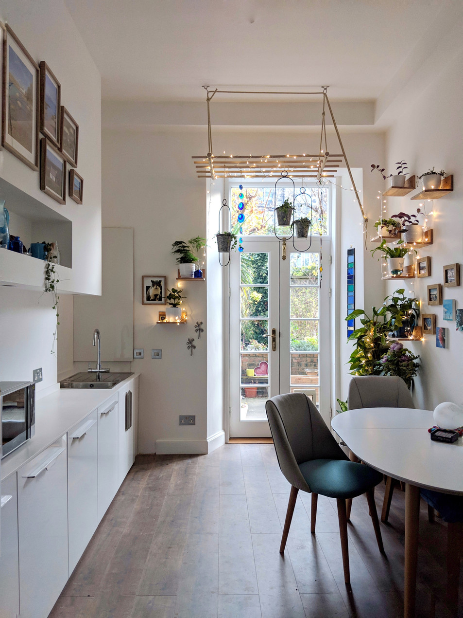 White kitchen with many plants on ceiling and wall. Glazed doors into garden.