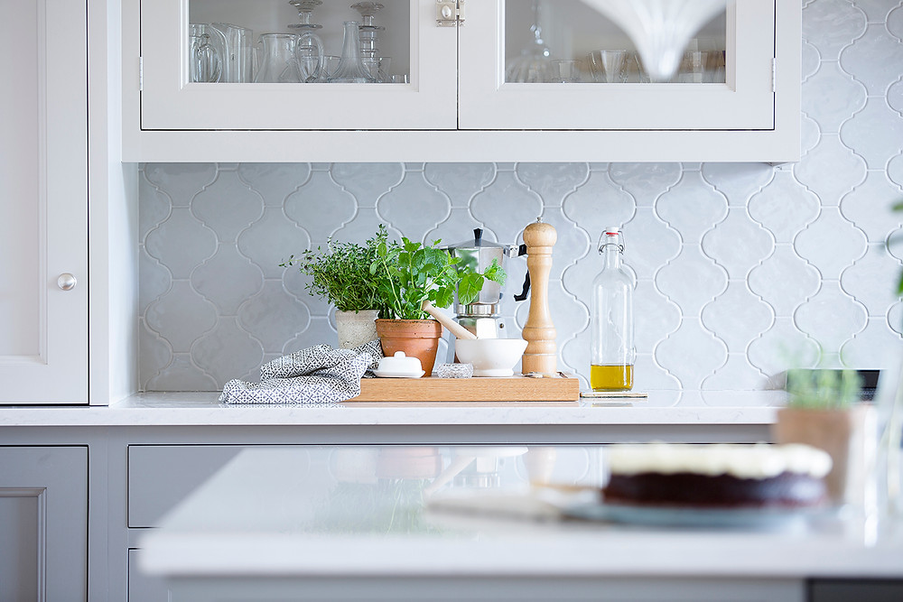 In a glossy grey kitchen, green herbs sit in rustic pots on a wooden chopping board with a pepper grinder, bottle of oil and dish cloth. The wall tiles are in arabesque formation
