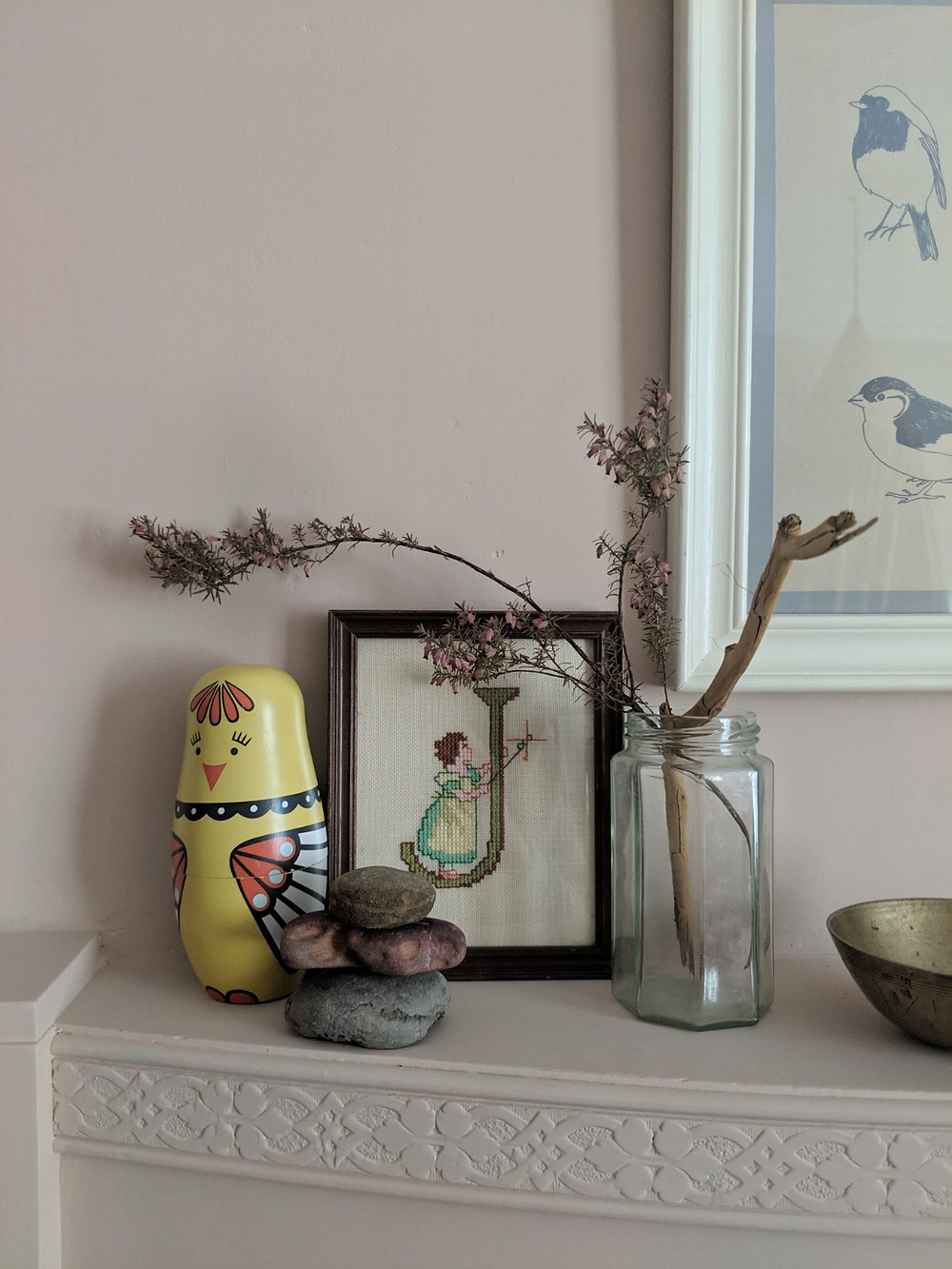 Children's treasures arranged on a pink mantelpiece