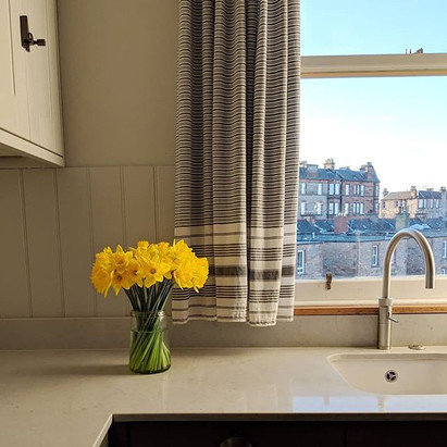 A vase of daffodils on a kitchen counter by a window dressed with stripey curtains.
