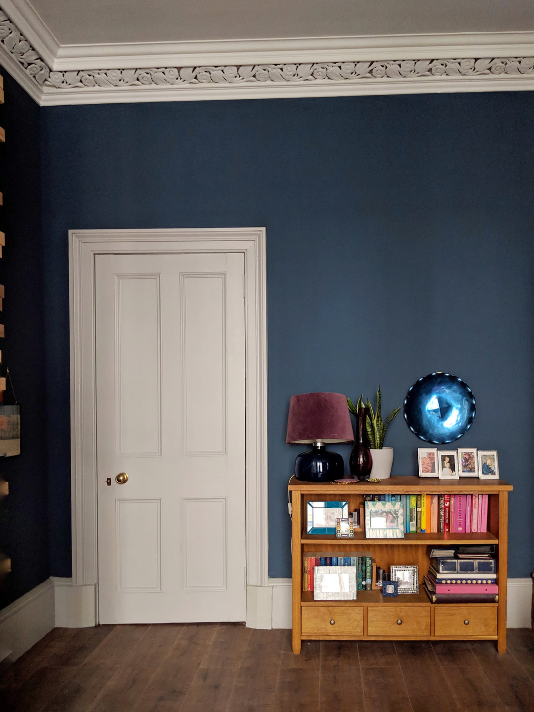Bright accessories styled on a bookcase with a dark blue wall and grey door