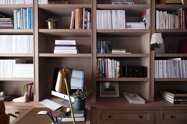 Wooden study shelving full of books and objects.